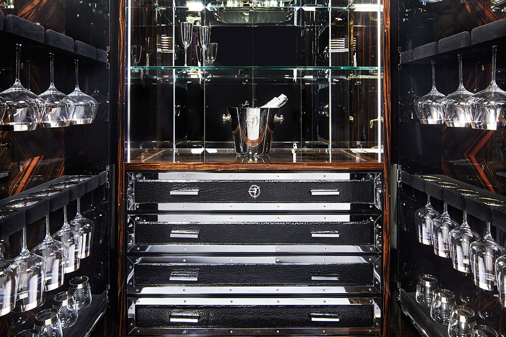 The piece contains crystal shelves and cutlery drawers