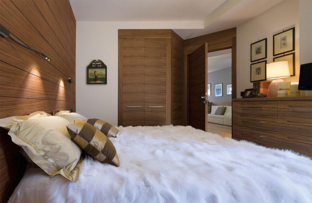 Full height paneling, corner wardrobe and matching furniture create a unique interior
