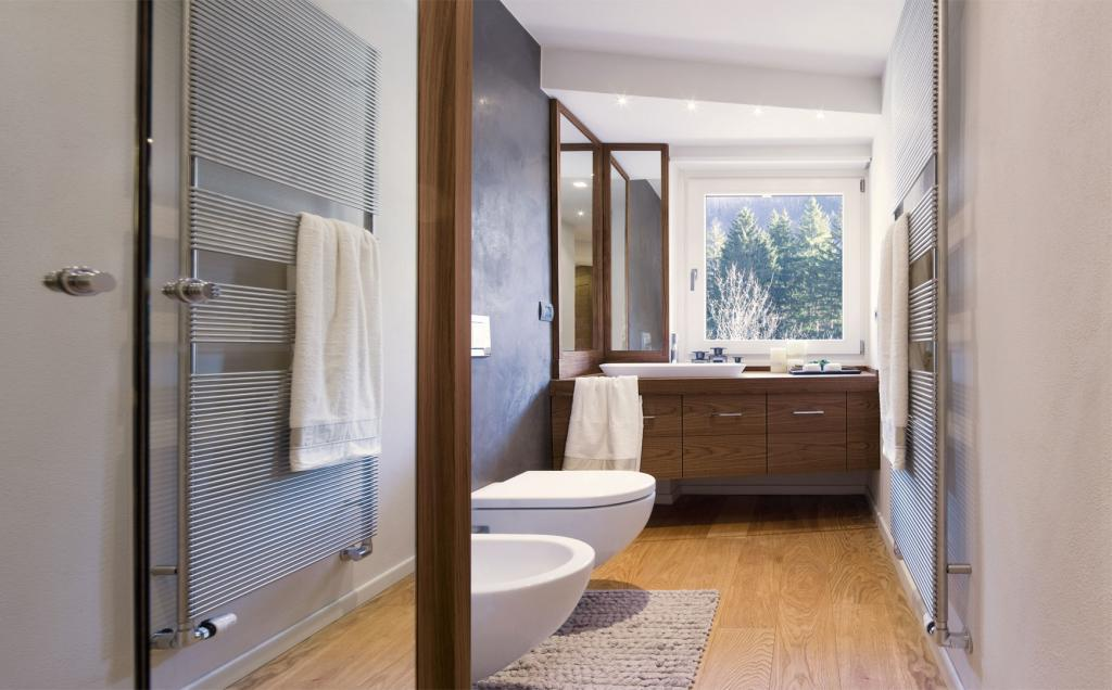 A contemporary bathroom where oak flooring and walnut sink furniture are in harmony
