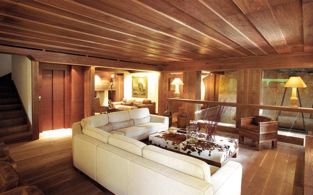 Solution with matching ceiling, flooring and paneling enriched by the spacious corner sofa