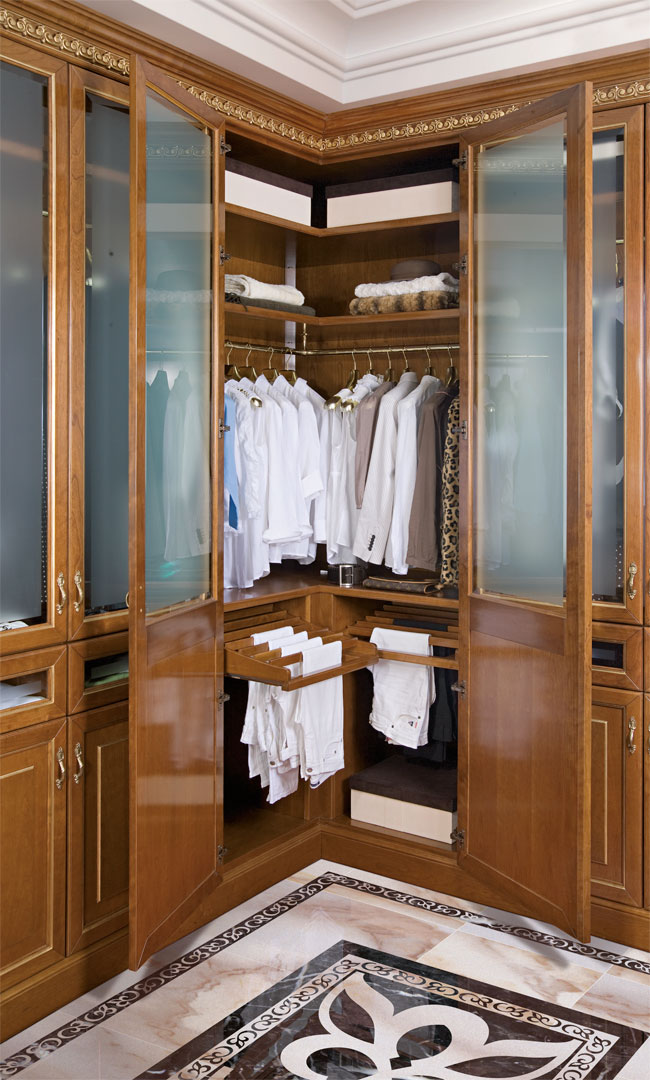 Corner of walk in wardrobe with pull- out trouser rack