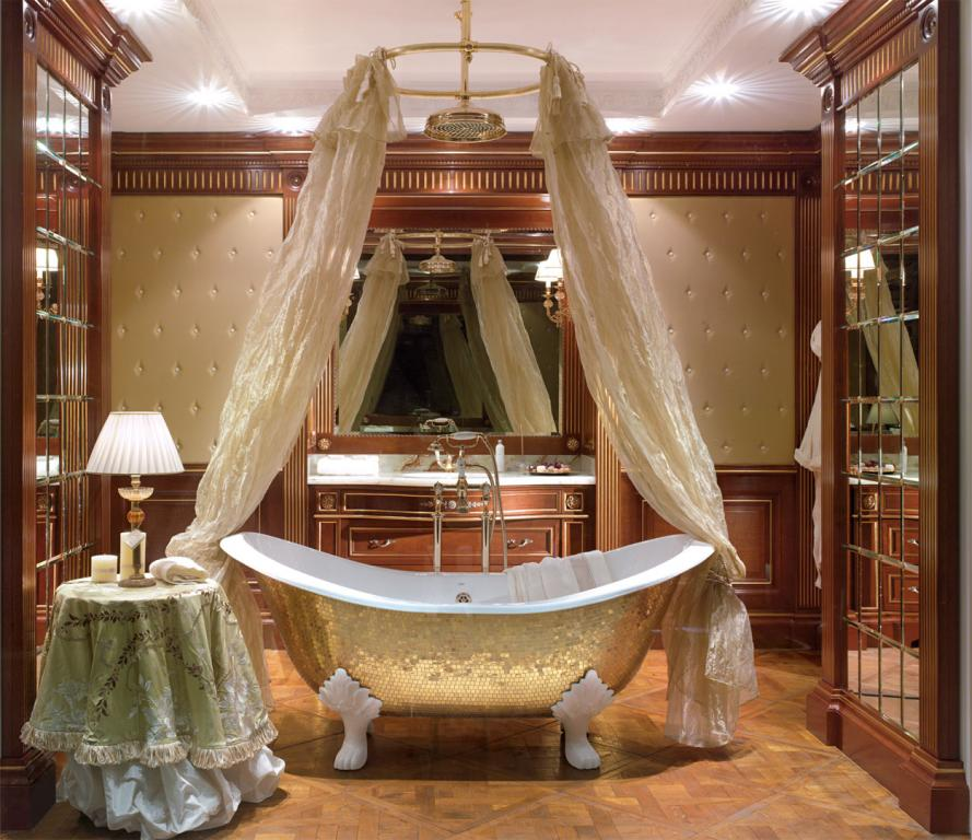 Glass golden mosaic bath tub wrapped in a sumptuous ivory tulle curtain